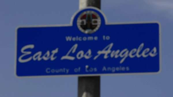 Rack focus on a Welcome to East Los Angeles sign at Belvedere Community Regional Park in East Los Angeles, California. Royalty-free stock video