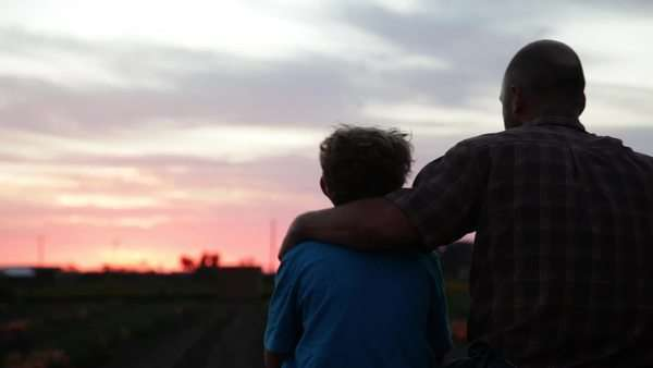 A father and son sit in a farm field at sunset. Royalty-free stock video