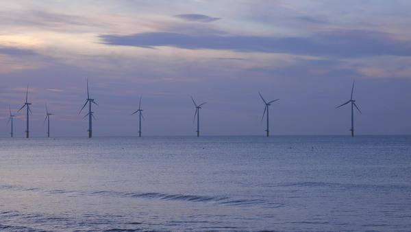 A wind farm generates electricity along a coastline at sunset. Royalty-free stock video