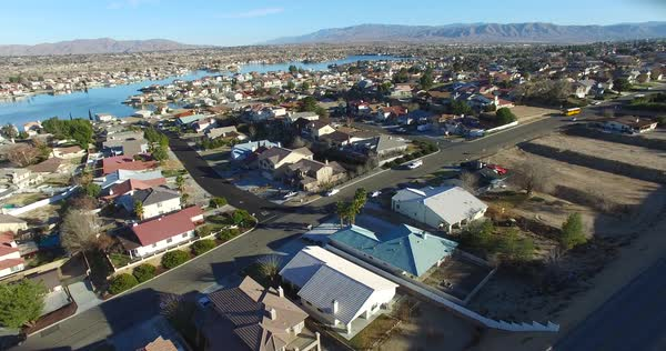 Aerial over a suburban neighborhood in the desert with an artificial lake distant. Royalty-free stock video