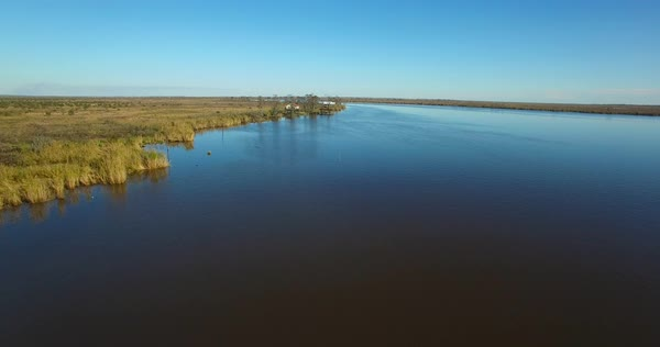 An aerial over the Louisiana bayou reveals a house on stilts. Royalty-free stock video