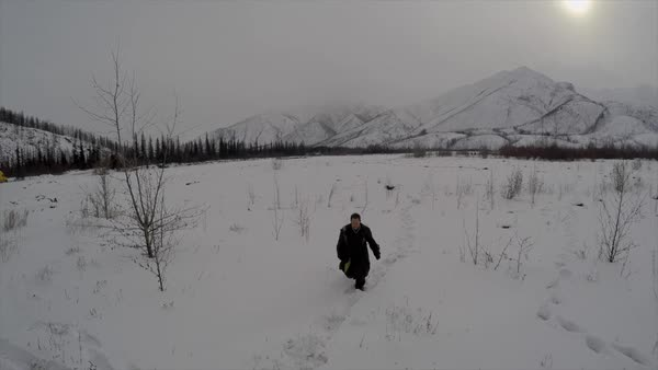 A man is lost and runs through a snowy landscape in the arctic. Royalty-free stock video