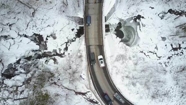 An aerial POV perspective looking straight down on a car traveling on a highway through a frozen wilderness. Royalty-free stock video