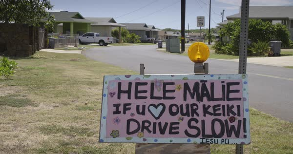 A sign in a Hawaiian neighborhood urges people to slow down and respect safety. Royalty-free stock video