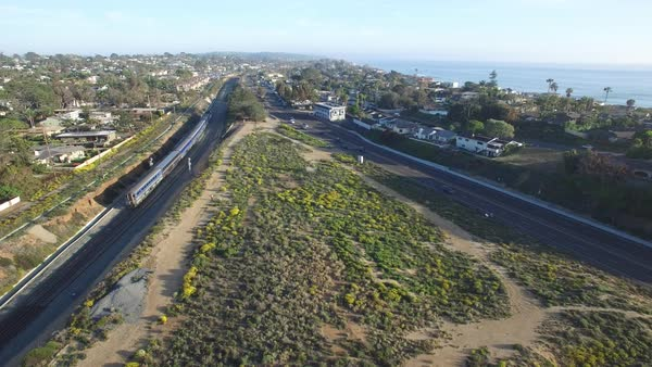 High stationary aerial over an Amtrak train traveling beside the Pacific ocean near San Diego. Royalty-free stock video