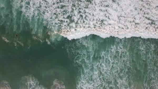 An aerial perspective looking straight down at the ocean with waves rolling in. Royalty-free stock video