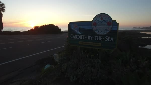 An aerial over a sign welcoming visitors to Cardiff By The Sea in San Diego reveals the beach at sunset. Royalty-free stock video