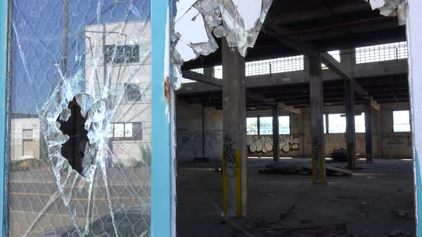 Interior of an old factory or warehouse with broken window foreground. Royalty-free stock video