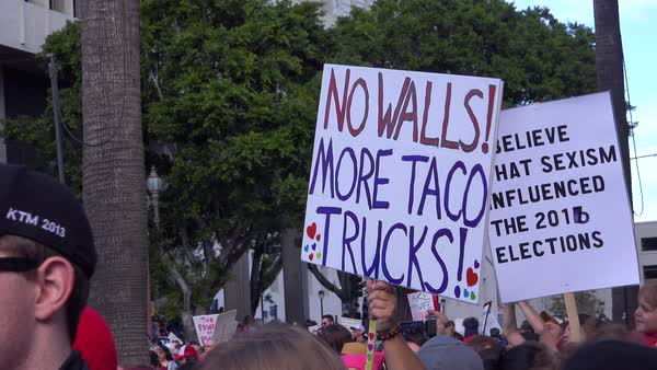 A huge protest against the presidency of Donald Trump in downtown Los Angeles with sign saying no walls more taco trucks. Royalty-free stock video