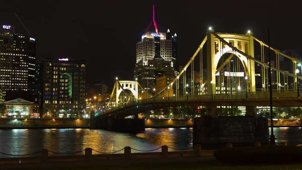A colorful city timelapse of Pittsburgh, Pennsylvania, USA at night, featuring the iconic Roberto Clemente bridge, a busy highway and several illuminated buildings. Wide shot from waterfront with no camera movement. Royalty-free stock video