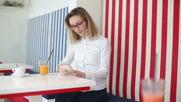 Young woman wearing white shirt and eyeglasses, smiling and browsing on mobile phone at the coffee shop shile having orange juice. Coffee on the table. Medium wide shot. Camera slides right to left Royalty-free stock video