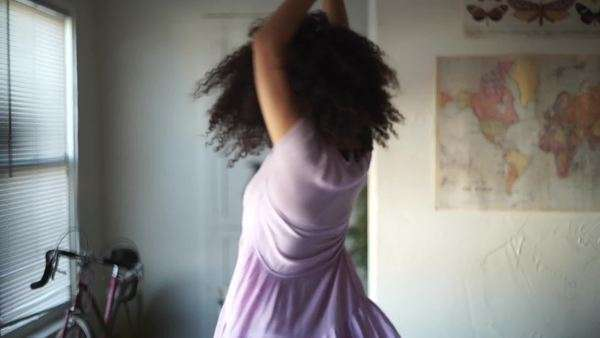 Handheld shot of a young woman twirling indoors, showing off her purple dress Royalty-free stock video