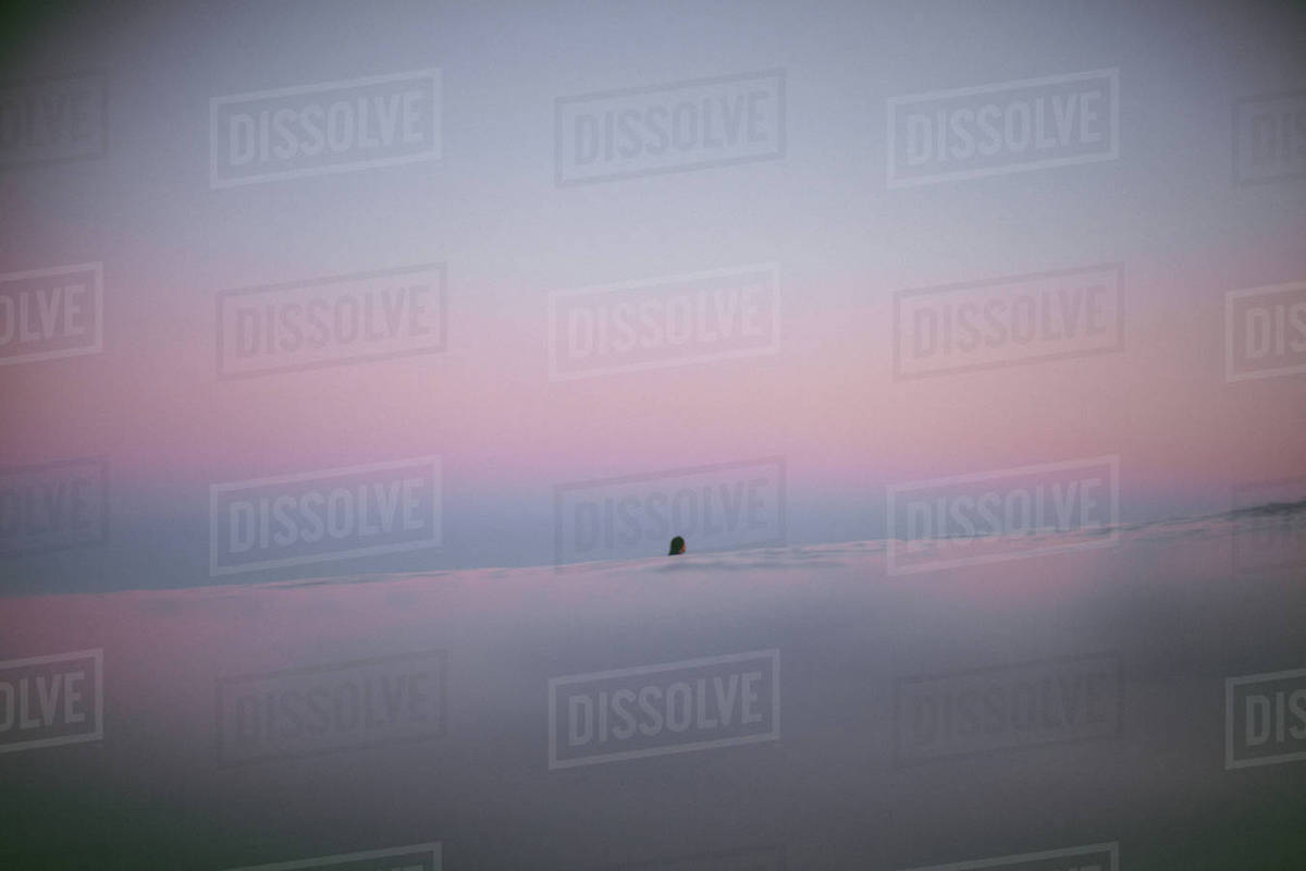 Woman in ocean at sunset Royalty-free stock photo