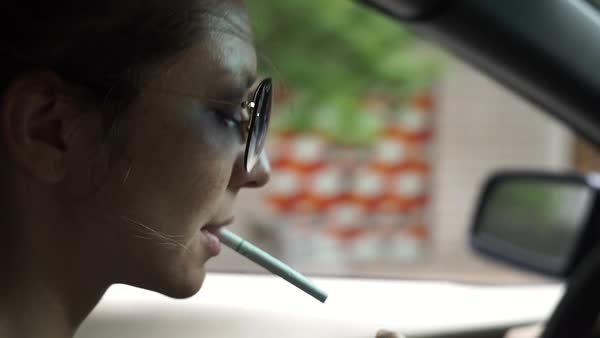 0a273dfd2f95 Close-up shot of a young woman lighting a cigarette while driving a car  Royalty
