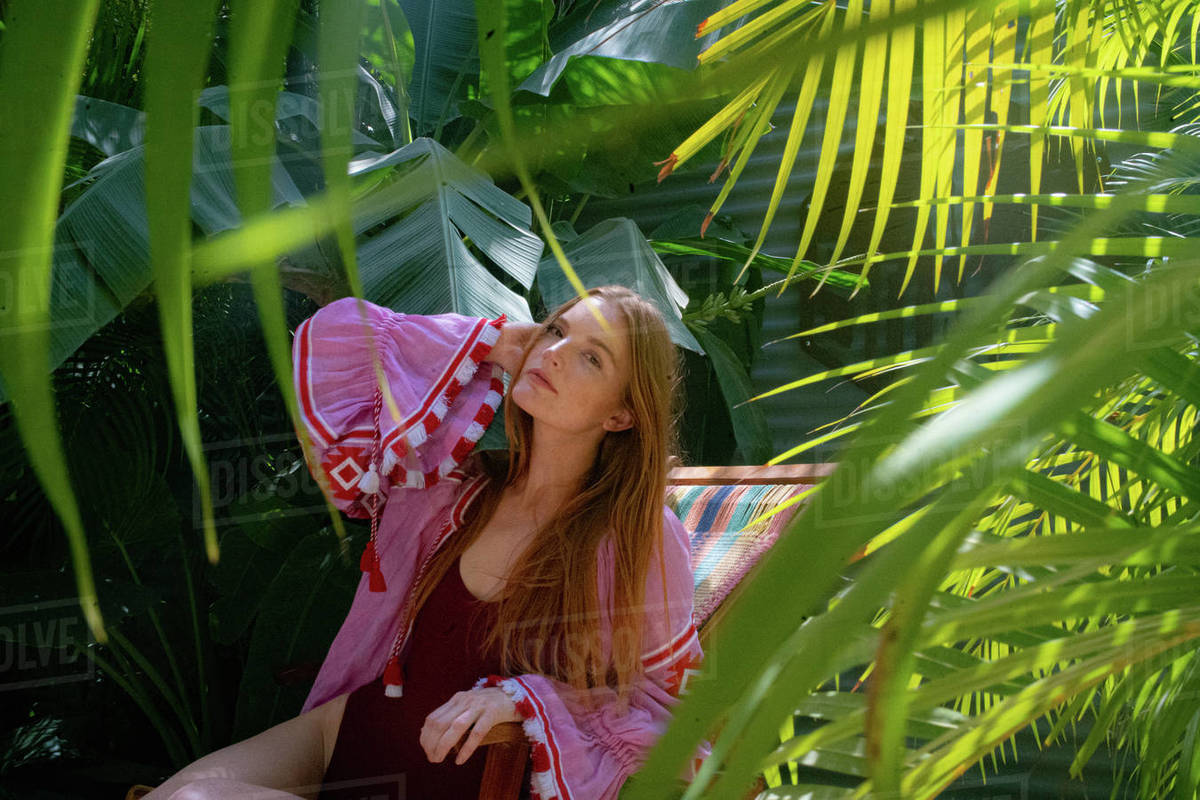 Portrait of a young woman sitting on reclining chair surrounded by plants at resort Royalty-free stock photo
