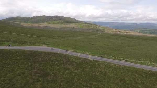 Aerial tracking shot of a group of cyclists going down a road in the Scottish highlands Royalty-free stock video