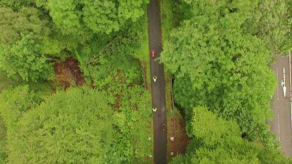 Aerial shot of a group of cyclists riding through a forest in Scotland  Royalty-free stock video