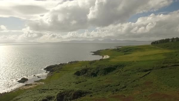 Stunning aerial shot along the coast of Scotland with Eigg and Rum islands in the background Royalty-free stock video