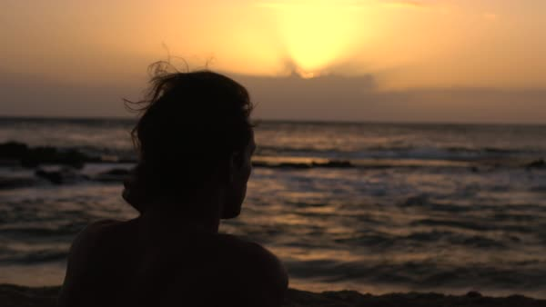 Hand-held shot of a man sitting on a beach at sunset Royalty-free stock video