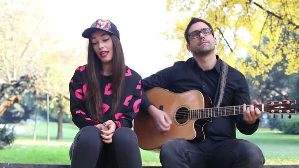 Close-up of beautiful young couple playing guitar and singing while sitting on a tree in park, graded Royalty-free stock video