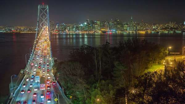 Timelapse of traffic on Oakland Bay Bridge and San Francisco skyline at night. Zoom in. Royalty-free stock video