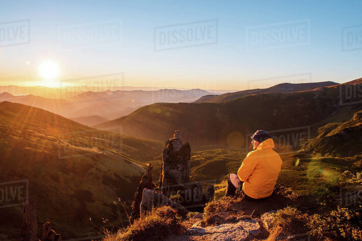 Back view of young man in yellow jacket sitting on peak of mountains and enjoying amazing summer sunset. Concept of extreme vacation. Royalty-free stock photo