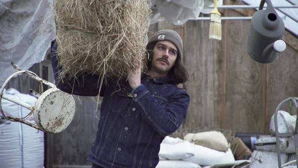 Man carrying hay bale through barn as objects float Royalty-free stock video