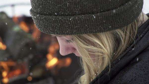 Slow motion young woman sitting by fire in snow Royalty-free stock video