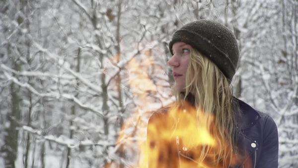 Slow motion young woman sitting in snow with fire in foreground Royalty-free stock video