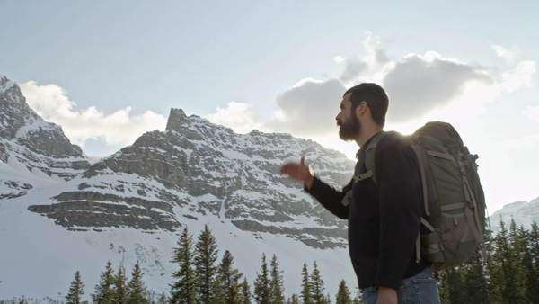 Man shields sun from eyes in front of snowy mountains Royalty-free stock video