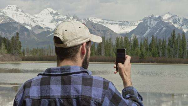 Man uses phone in front of lake with mountains in distance Royalty-free stock video