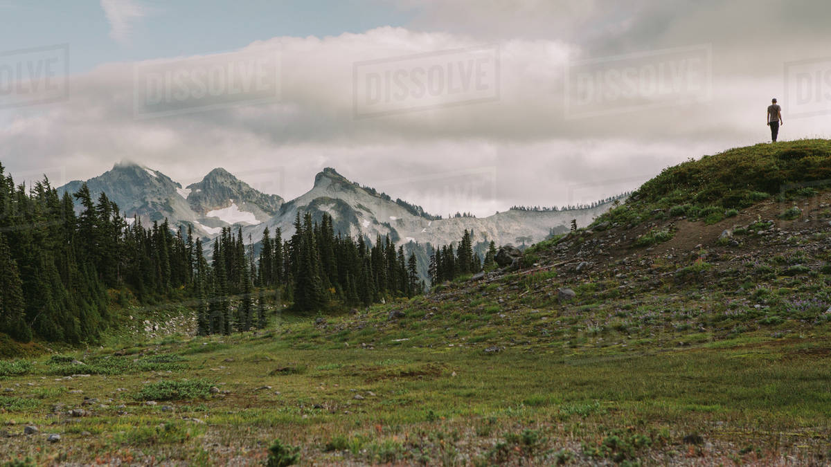 Person walking in the distance in front of mountain scape  Royalty-free stock photo