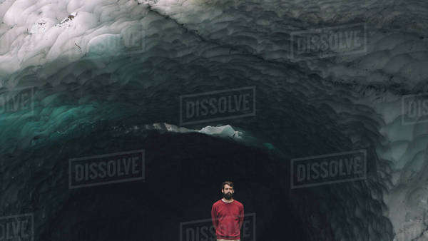 Man in red sweatshirt poses in front of enormous ice cave Royalty-free stock photo