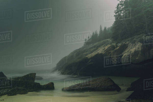 Waves breaking over rocks in fog Royalty-free stock photo
