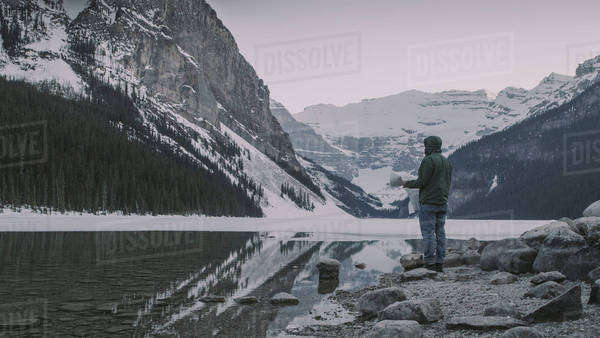Man with map stands in front of reflective lake with mountains in background Royalty-free stock photo