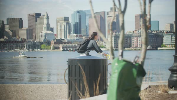 Young woman rides bike in front of Boston skyline Royalty-free stock video