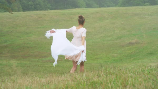 A woman holding shawl and running on grassy landscapeand smiling Royalty-free stock video