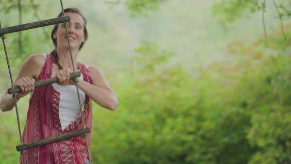 A young woman swinging on rope swing and smiling Royalty-free stock video