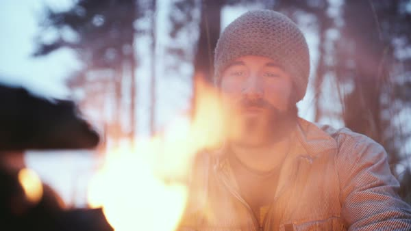 Hand-held shot of a man gazing at a campfire Royalty-free stock video