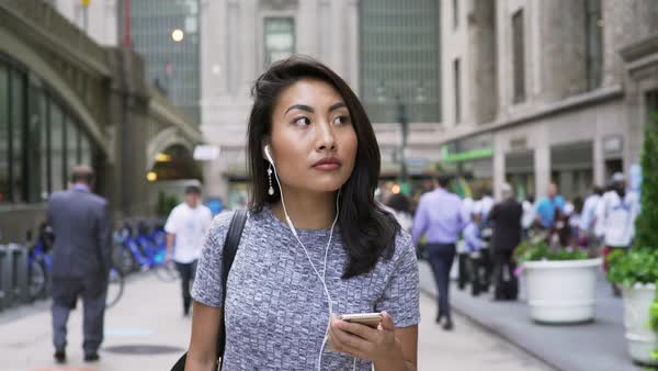 Tracking shot of a woman walking with earphones Royalty-free stock video