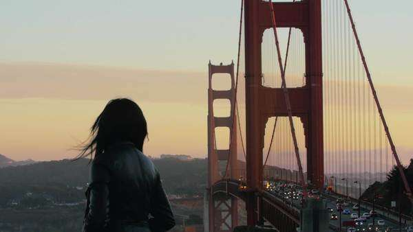 Woman looks out at San Francisco during sunset with traffic in background. Royalty-free stock video
