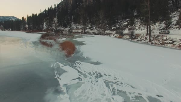 Tracking shot of a car driving alongside a frozen river Royalty-free stock video