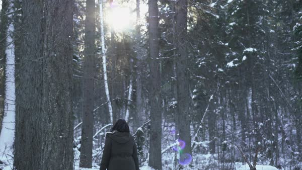 Panning shot of a young woman turning around in a snow covered forest Royalty-free stock video