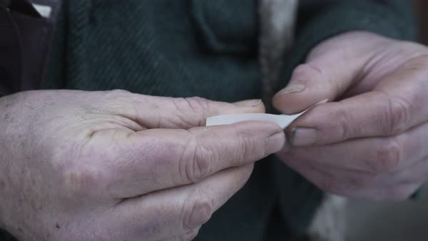 Hand-held shot of a man rolling a cigarette Royalty-free stock video