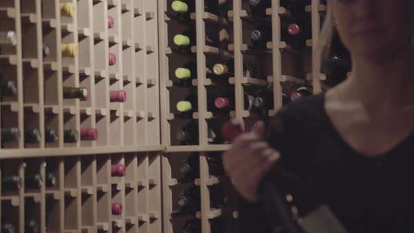 Hand-held shot view of a woman taking a bottle from the wine cellar Royalty-free stock video