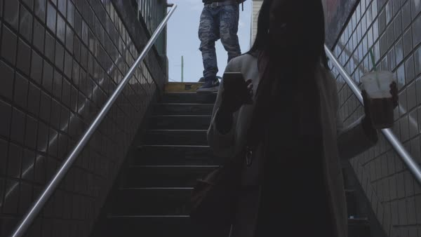 Hand-held shot of a woman walking down subway stairs Royalty-free stock video