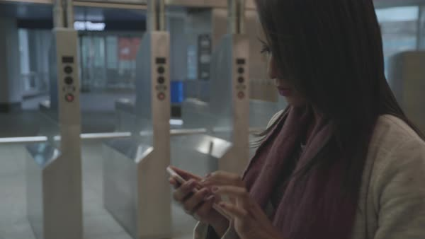 Tracking shot of a woman using her cell phone in a subway passage Royalty-free stock video