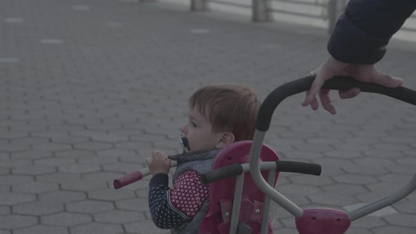 Hand-held shot of a man pushing a baby bike by East River Royalty-free stock video