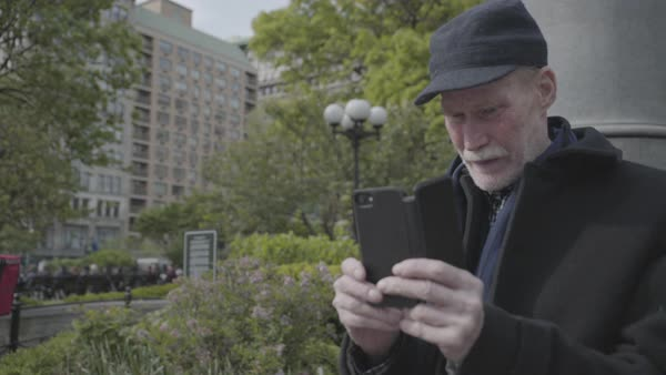 Hand-held shot of an elderly man using his smartphone in a park Royalty-free stock video