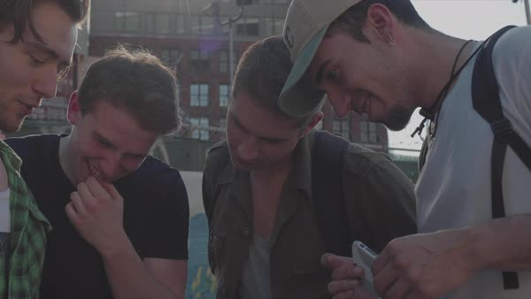 Hand-held shot of four young men looking at a smartphone outside Royalty-free stock video